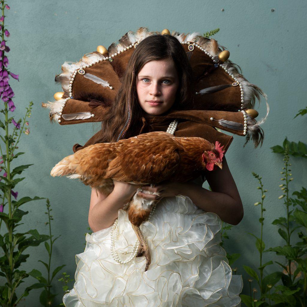 Fineart portret van meisje met kip op haar arm met slider naar rechts en links in voor en nabewerking