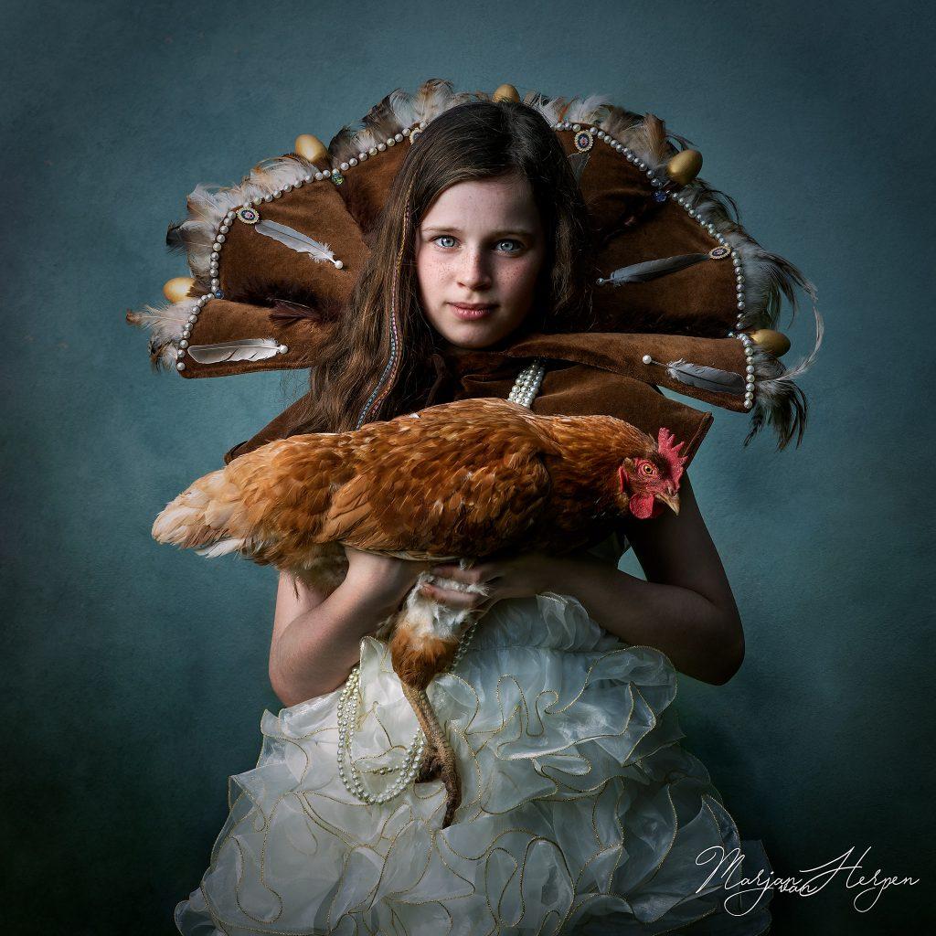 Fineart portret van meisje met grote kraag met veren en gouden eieren en haar kip op de arm als voorbeeld voor een te boeken kinderportret in Venlo