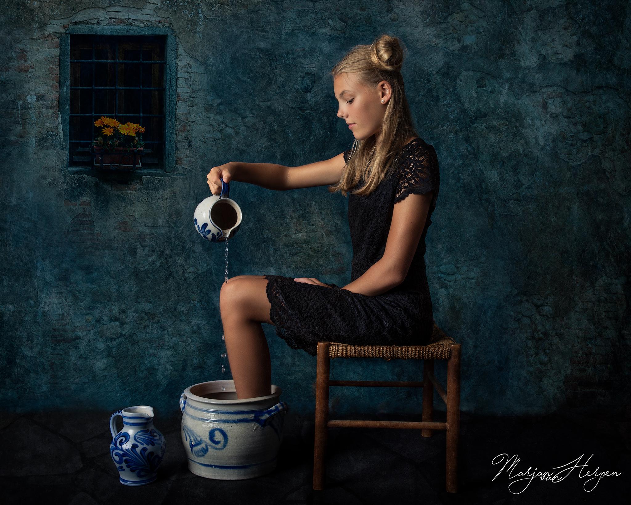 Fineart portret van meisje met voeten in aardwerken pot die water schenkt